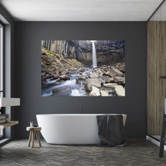 very large fine art print of waterfall in Iceland displayed above bathtub in bathroom of modern stylish luxury home