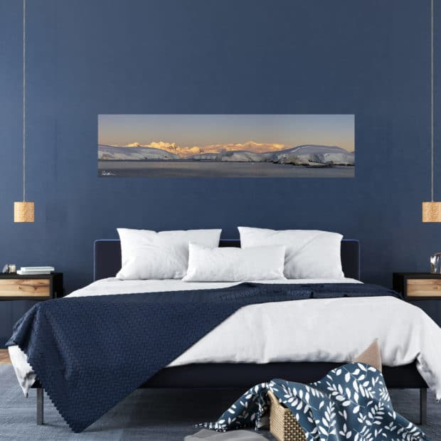 panoramic photo of a sunset across mountains in Antarctica displayed in bedroom of stylish home