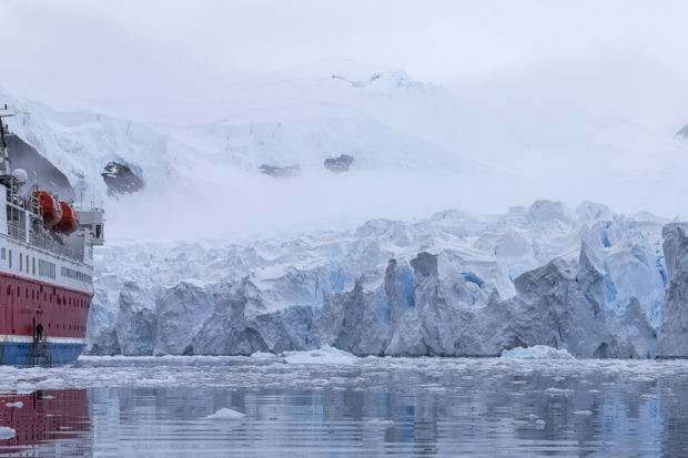 ship in front of large antarctic glacier
