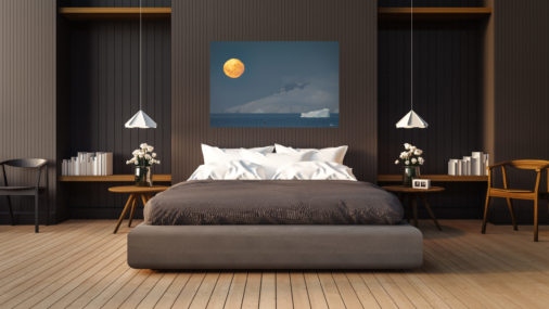 large photo of moon rising over mountains with a whale jumping displayed in a bedroom of a luxury home