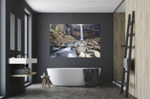 large fine art print of waterfall displayed above bathtub in modern luxury home