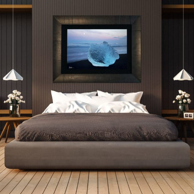 large fine art print of glowing blue ice on black sand beach in Iceland displayed in modern stylish luxury home