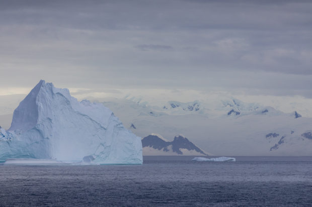 very large iceberg floating by mountains