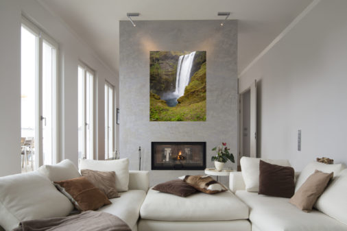 large photo of Icelandic waterfall displayed above fireplace in modern luxury home