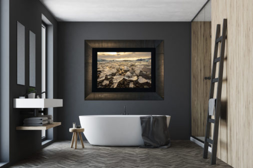 framed photo of ice in glacier bay displayed above bathtub in bathroom of modern luxury home