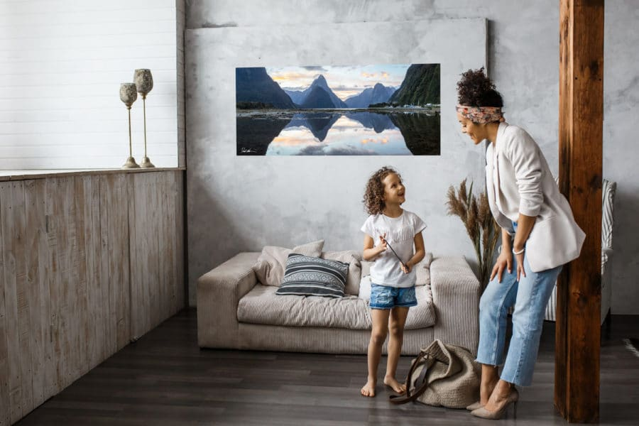 beautiful mountain photo hung in modern home with happy relaxed mother and daughter smiling