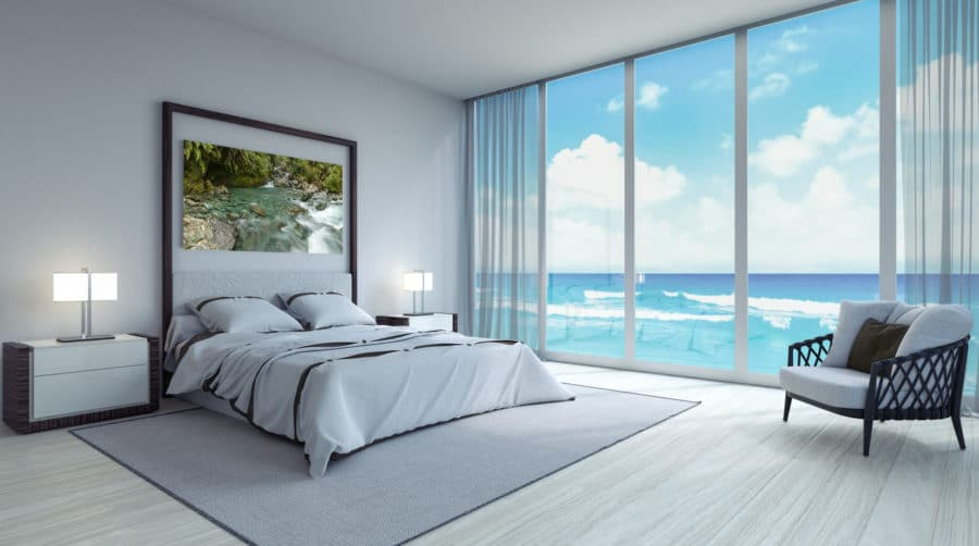 a calming stress free ocean bedroom with nature driven art above the bed looking out over the calm blue ocean