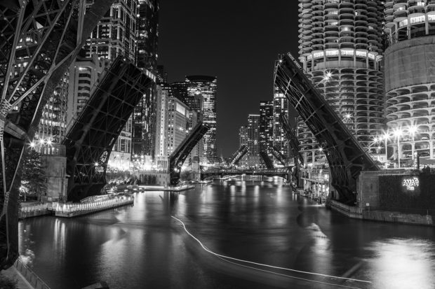 Black and white photo of the Chicago river downtown at night with its bridges up