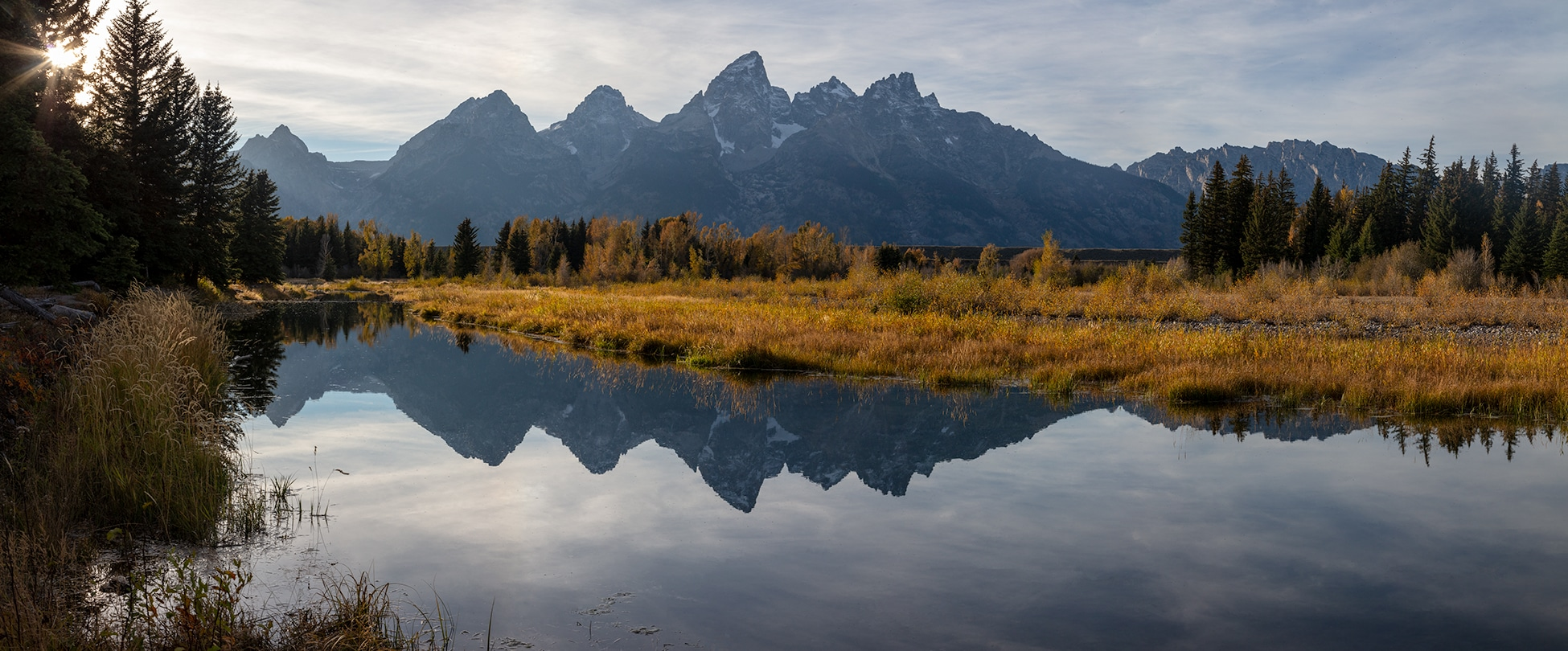 Photograph of the Grand Teton mountain range with a reflection over a river
