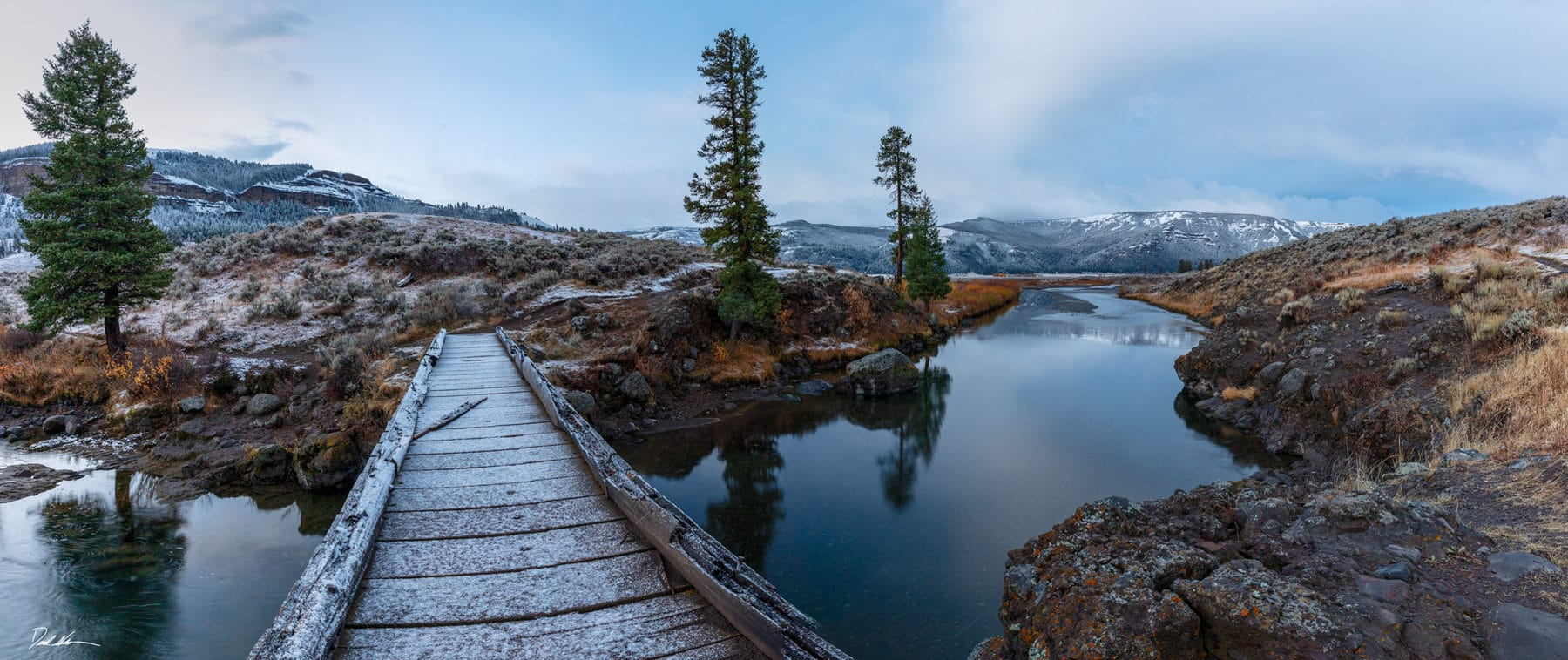 a frost covered bridge crossing a stream in Yellowstone National Park