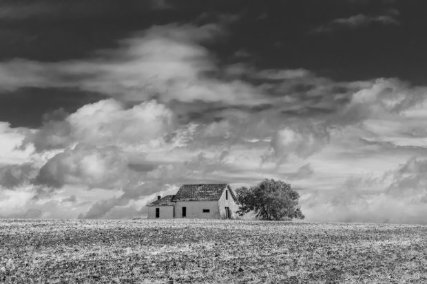 black and white photo of an old barn on an empty field