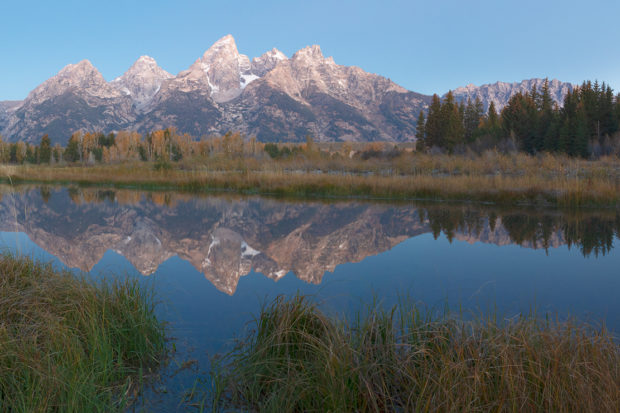 Reflection of Teton mountains at dawn over a small river