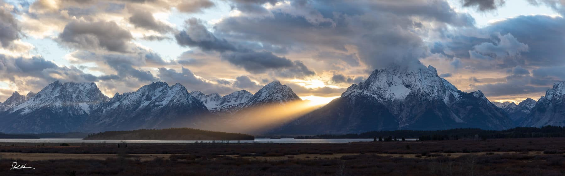 a sunbeam splits the Tetons mountains at sunset