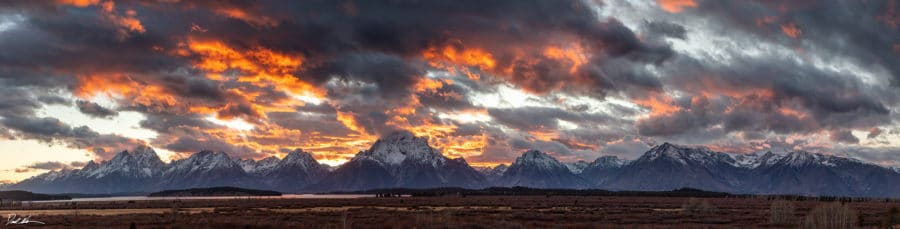 panoramic image of Teton range at sunset with dramatic sky