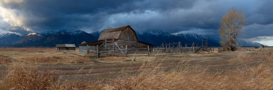 panoramic photo of old barn in front of the Grand Teton Mountains