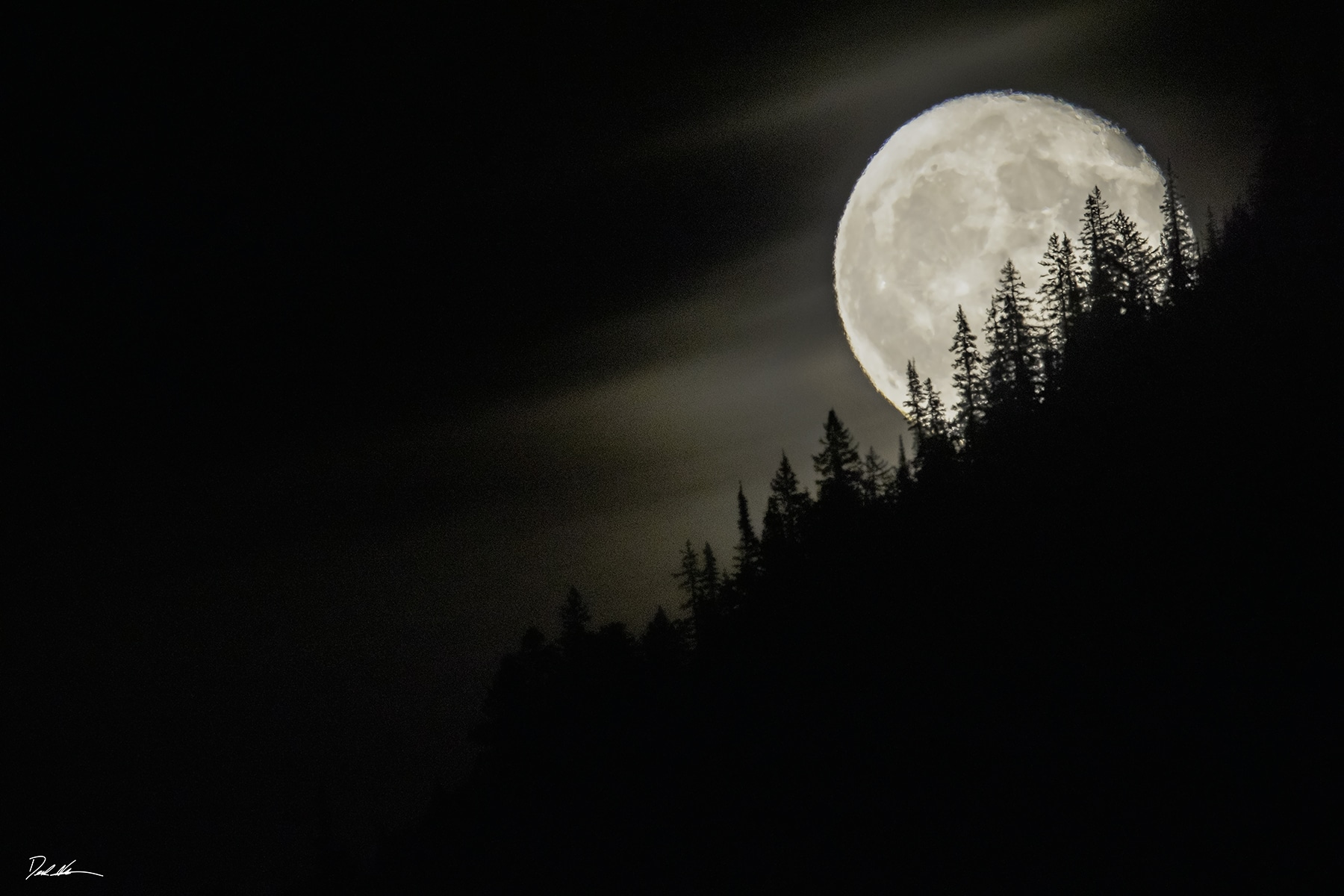 photo of full moon rising over the mountains in Yellowstone National Park