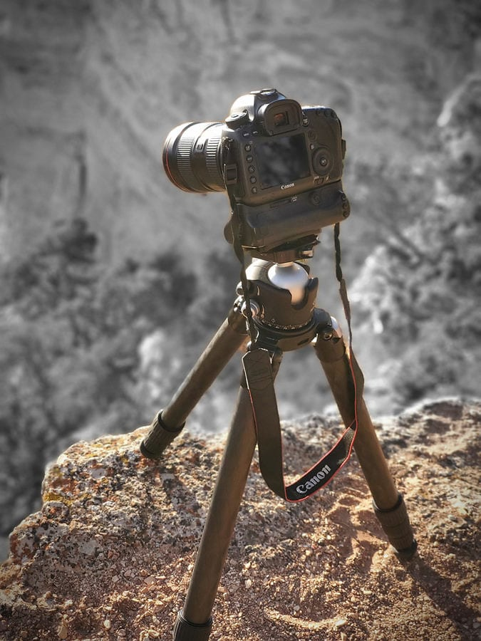 canon camera sitting on tripod at the edge of a canyon