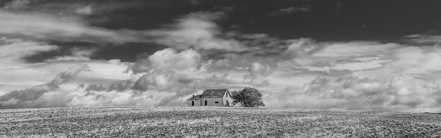 black and white image of a lone barn in a deserted western landscape with puffy clouds