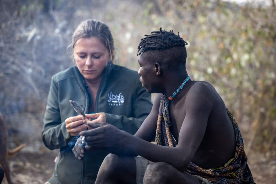 photo of tourist learning how to make an arrow from an African tribe member