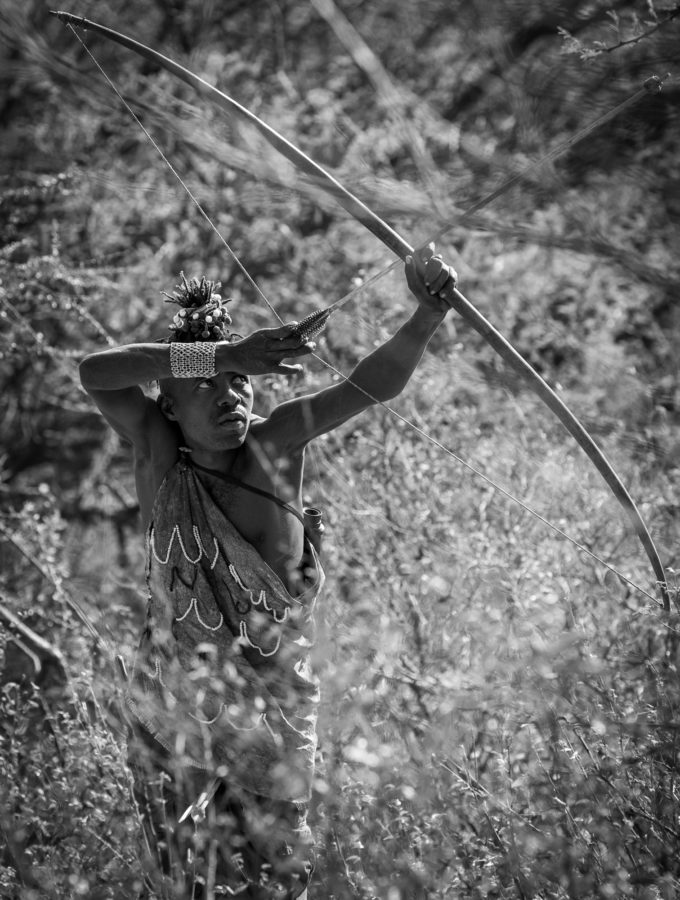 photo of African tribal chief getting ready to shoot an arrow from a bow