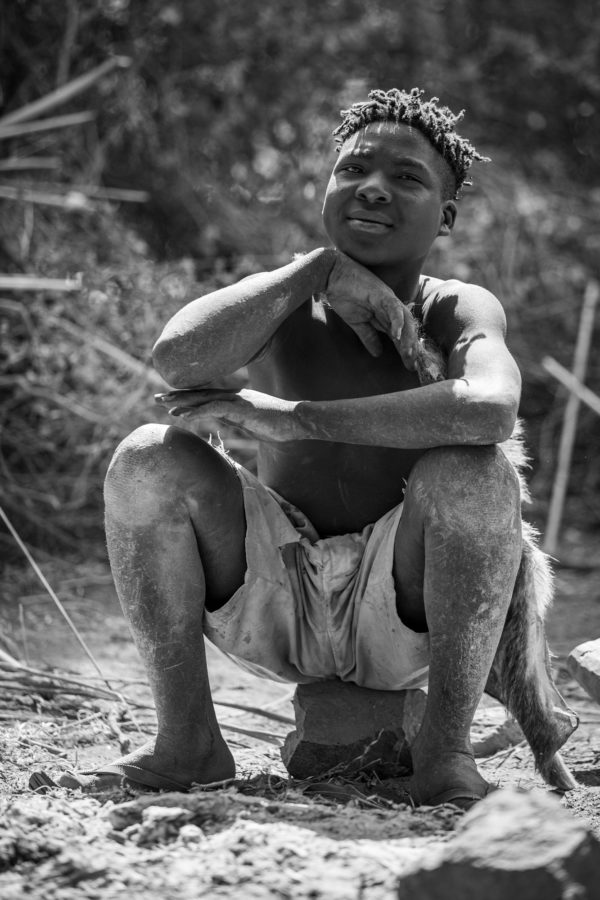 photo of young African tribal member sitting on a stone