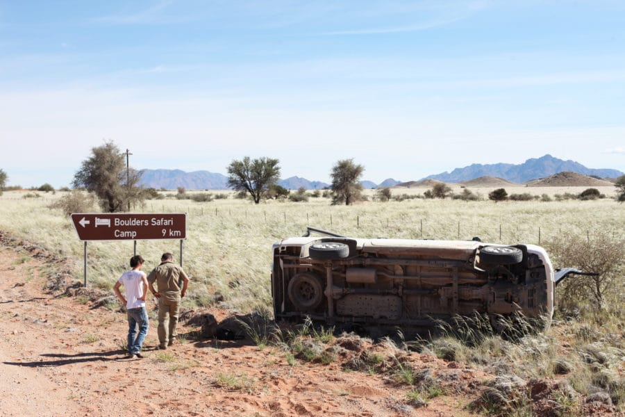 photo of safari vehicle flipped over with two people standing beside it