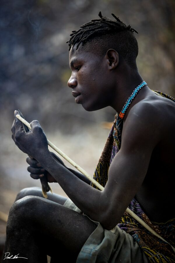 photograph of a young tribal member sharpening his arrow in Tanzania