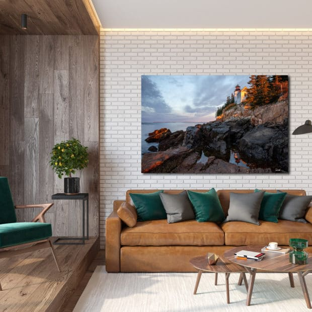 Large image of lighthouse in Maine displayed above a couch in living room of modern luxury home